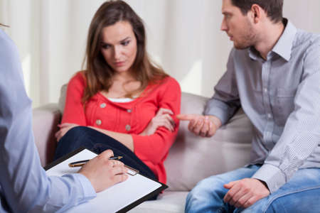 marriage counseling: Young man trying to talk with his angry wife on psychotherapy Stock Photo