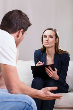 career counseling: Psychotherapist listening her patient very carefully in her cabinet Stock Photo