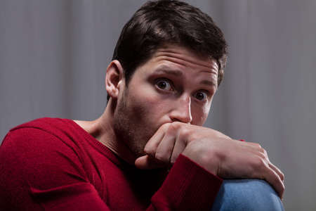 Young man with mental disease sitting curled up and scared Stock Photo - 30024003