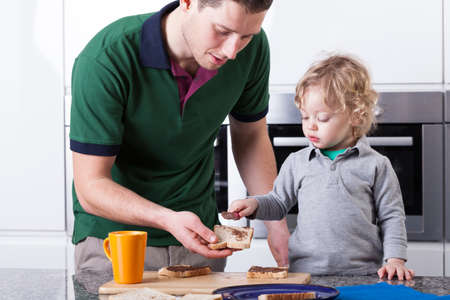 making fun: Father and son making sandwiches for breakfast together Stock Photo