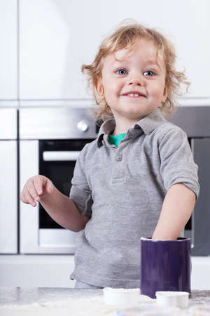Little child having good time in kitchen photo
