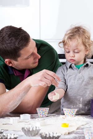 Man and little boy playing in kitchen photo