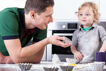 Young father helping little son baking muffins photo