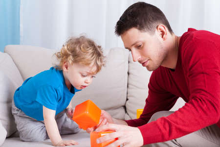 babysitting: Man and little boy playing with toys together Stock Photo