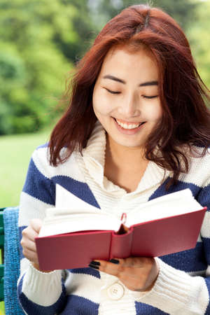 one story: Smiley asian girl reading book in the park