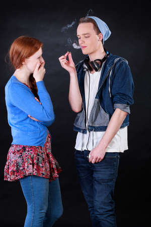 Teenage boy showing friend how to smoke joint photo
