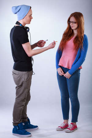 unkind: Rude boy giving girl a joint and inducing to smoke Stock Photo
