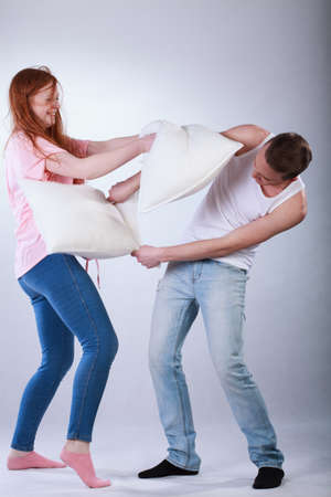 Cute rude teenagers fighting with pillows on isolated background Stock Photo - 30107840
