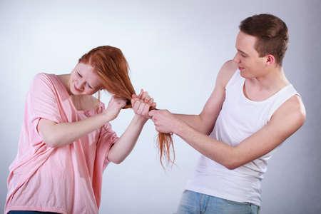 mischevious: Rude mischevious boy pulling his friend hair