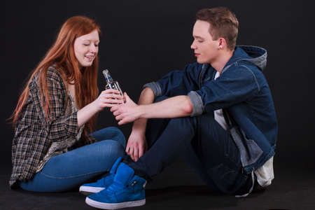 unkind: Naughty teenagers sitting on ground and drinking alcohol Stock Photo