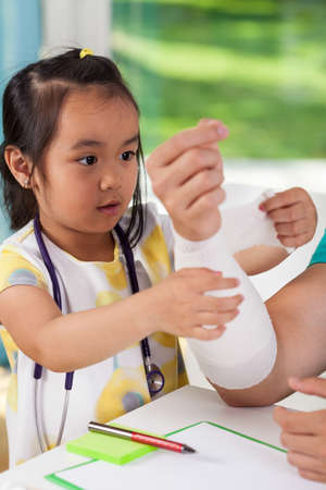 Little asian girl bandaging dads arm, vertical photo