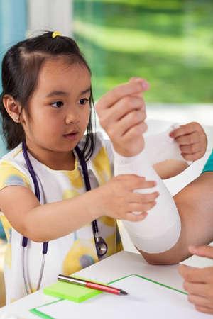 Little asian girl bandaging dads arm, vertical photo