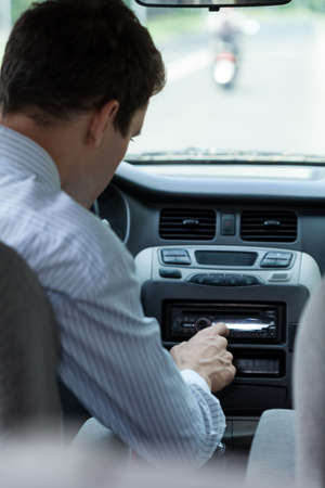 radio active: Man changing song in a car, vertical
