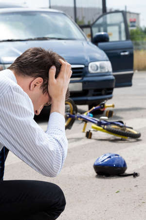 dissociation: Sad man after hitting little biker, vertical