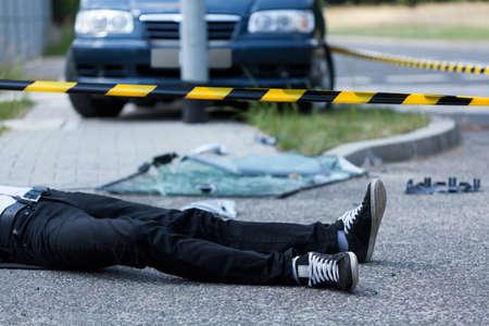 Man liggend op de straat na auto-ongeluk