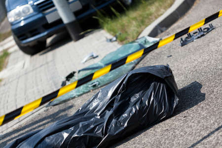 Car accident and corpse in bag, horizontal photo