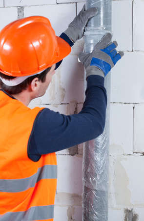 Close-up of a plumber working at construction site photo