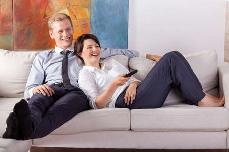 family business: Busy couple watching tv after work, horizontal Stock Photo