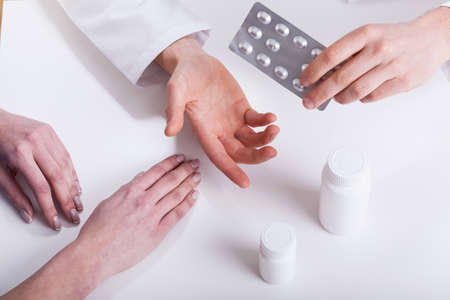 doctor giving pills: Doctor giving patient medicines closeup isolated hands photo