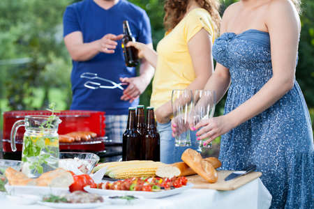 Young people grilling and having fun on garden barbecue party photo