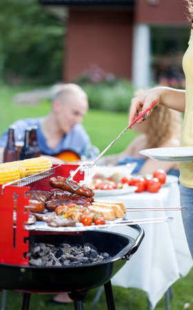Woman serving grilled sausages on barbecue garden party photo