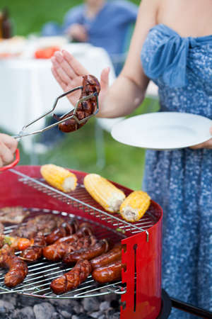 refusing: Woman on diet refusing grilled sausage on barbecue party