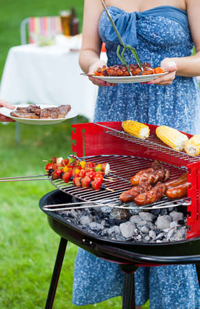 Woman taking grilled dishes to eat on garden party  photo