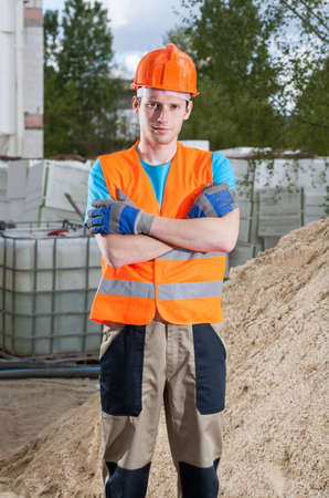 Vertical view of a builder standing with arms crossed photo