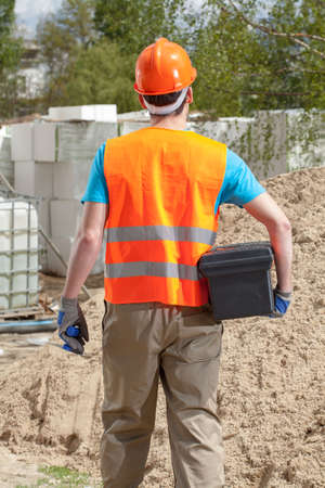 Back view of a blue-collar worker with toolbox and grout float photo
