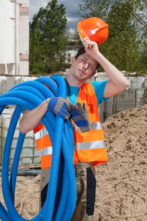 그의 어깨에 파이프를 들고 피곤 된 건설 노동자