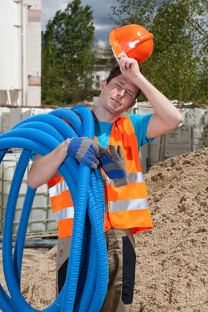 hot day: Tired construction worker holding pipes on his shoulder