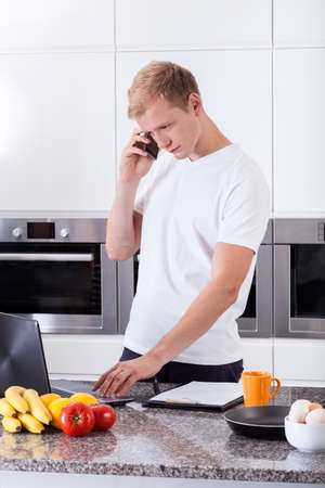 overworking: Busy man using computer in the kitchen Stock Photo