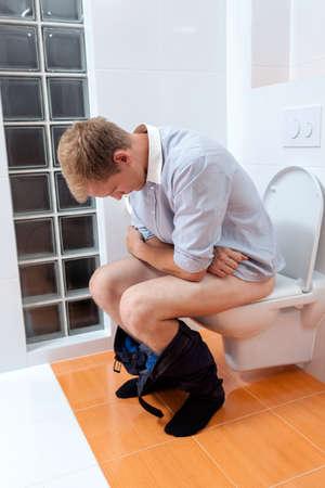 diarrea: Hombre en baño por la mañana en su casa, vertical