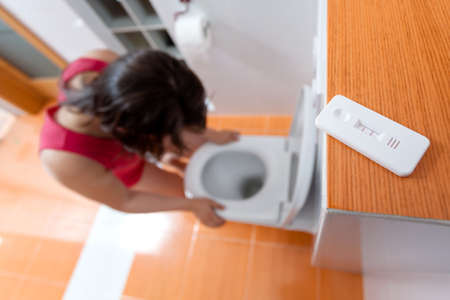 toilets: Pregnant woman with morning nausea in toilet Stock Photo