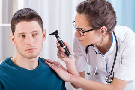 doctor examining woman: Young laryngologist examining patient by professional otoscope