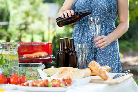 Woman pouring beer and preparing meals on barbecue photo