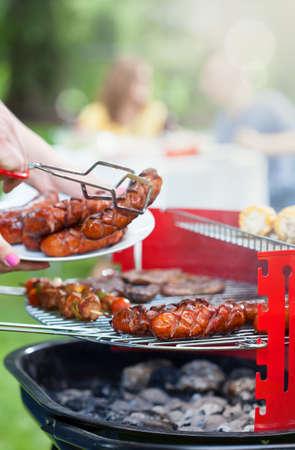 chorizos asados: Salchichas a la parrilla deliciosa porci�n de barbacoa en el jard�n Foto de archivo