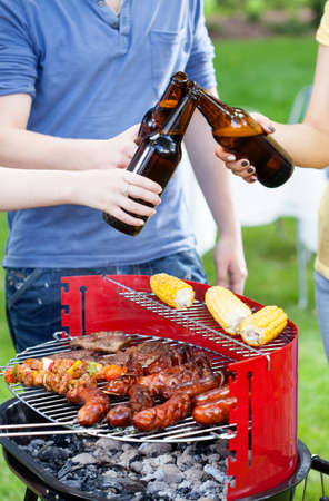 barbecue party: Friends having good time during grilling and drinking beer Stock Photo