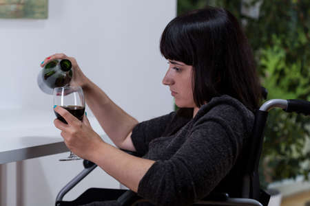 suffers: Disabled woman suffers from depression and drinks wine Stock Photo
