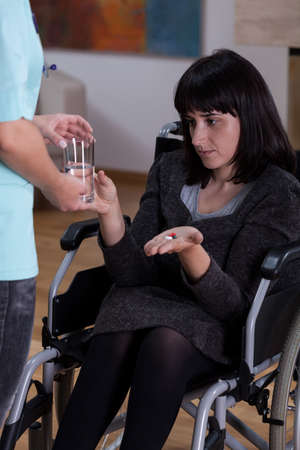disability insurance: Vertical view of disabled woman taking medicines