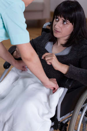 Nurse helps young woman on wheelchair, vertical photo