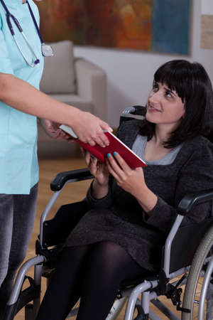Nurse giving a book to disabled woman photo