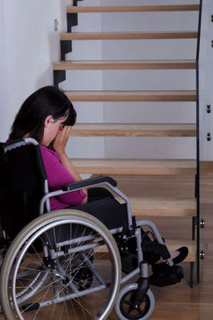 Disabled woman on wheelchair in front of stairs