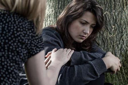 fille triste: Vue horizontale d'une femme soulageant son ami triste