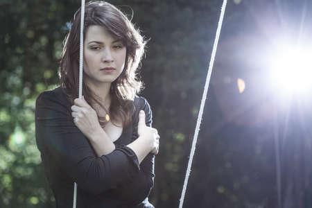 Eenzame jonge vrouw in verdriet zit op de schommel