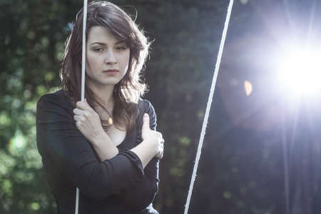 unhappy: Lonely young woman in sorrow sitting on the swing Stock Photo