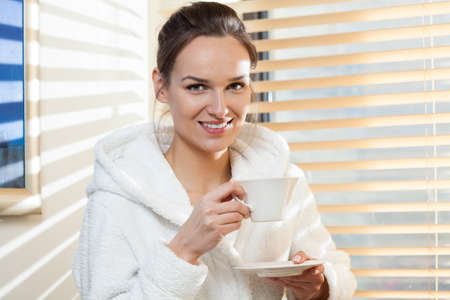 Woman drinking tea after treatment in spa photo
