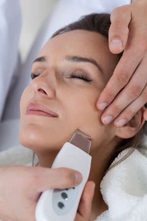 Close-up of woman having cavitation peeling, vertical Stock Photo
