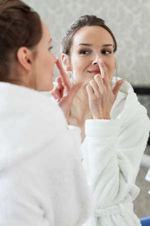 Woman looking in the mirror in spa photo