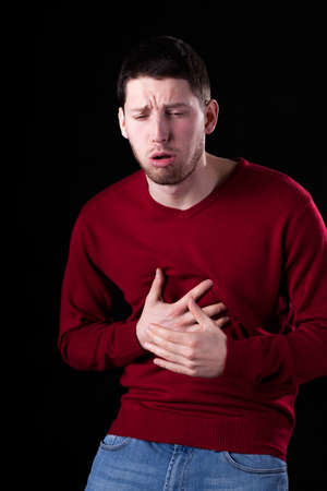 throe: Man with strong cough isolated on black